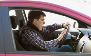 Closeup portrait of aggressive male driver honking in traffic jam
